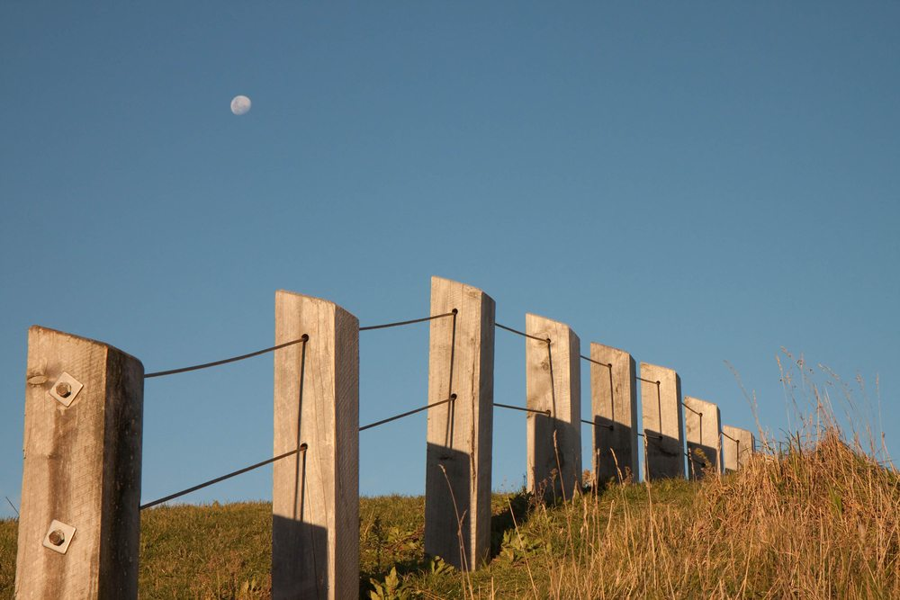 Queensland property with a fence running through it, against blue sky with low moon