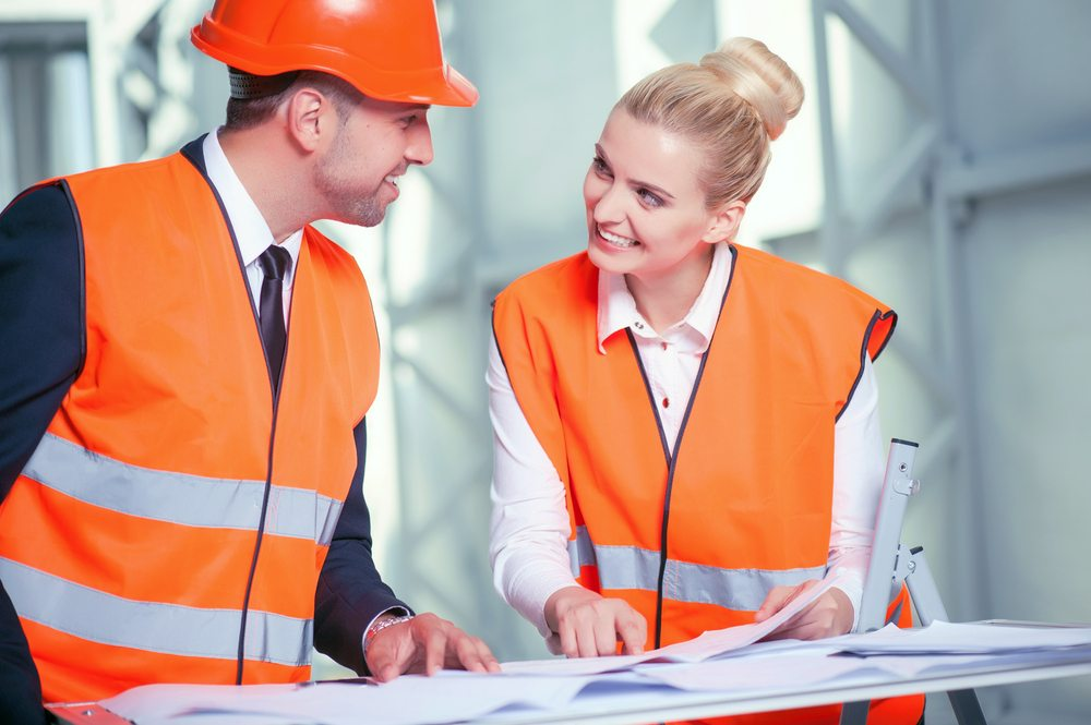 Two property development consultants in construction hi-vis looking over plans