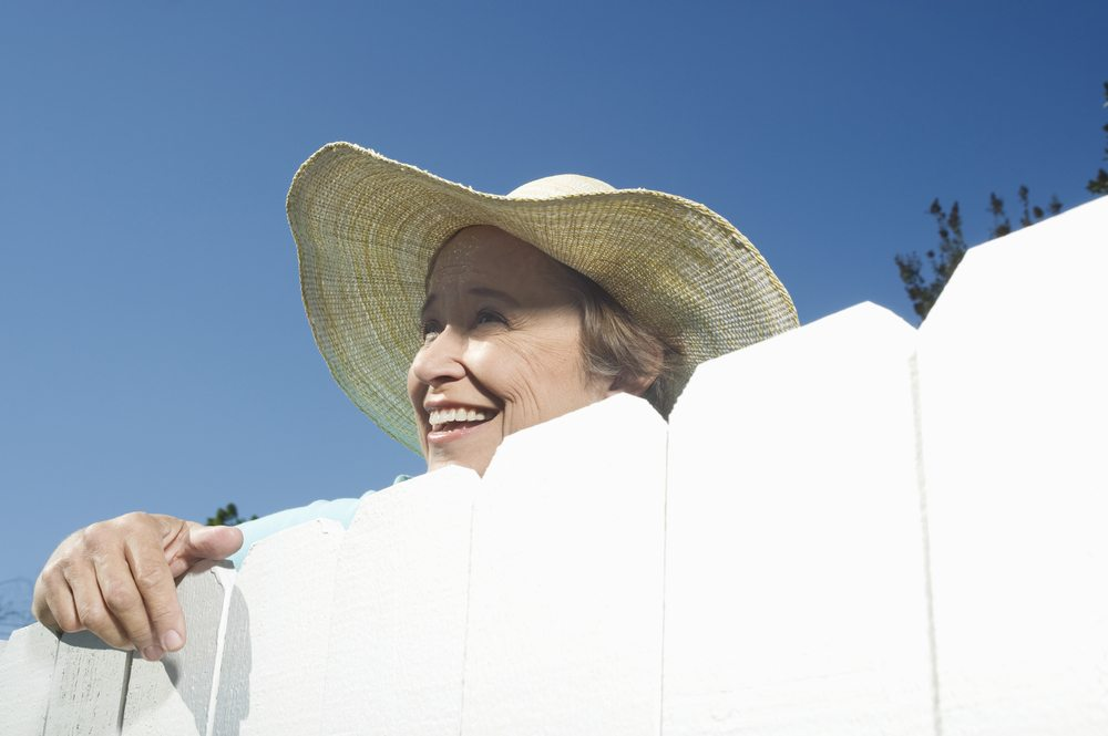 Woman smiling over garden fence