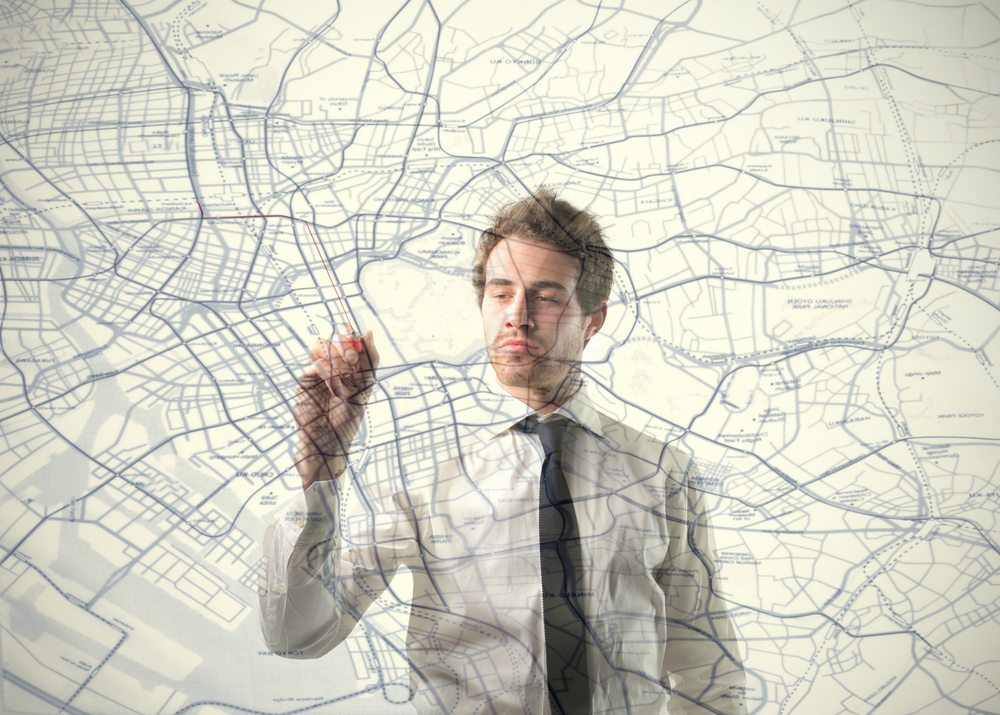 Man drawing on projection of town planning maps